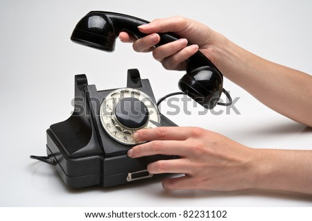woman hand hanging up the handset of an old black telephone isolated over white background - stock photo