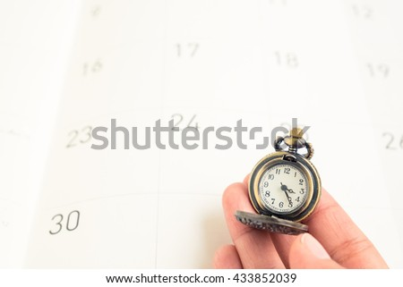 Woman hand hold a classic vintage necklace watch on calendar date paper - concept of time management - stock photo