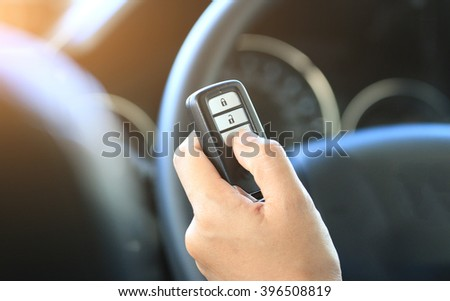 Woman hand hold a remote key car and push - stock photo