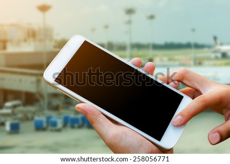 woman hand hold and touch screen smart phone,tablet,cellphone in cargo of  airport terminal - stock photo