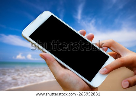 woman hand hold and touch screen smart phone, tablet,cellphone on blurred beautiful beach background.  - stock photo