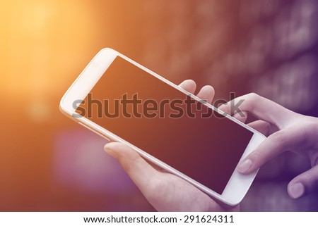 woman hand hold and touch screen smart phone,tablet,cellphone on stock chart market background,with filtered color. - stock photo