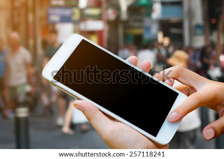 woman hand hold and touch screen smart phone,tablet,cellphone on street shopping with sun lighting of morning time. - stock photo