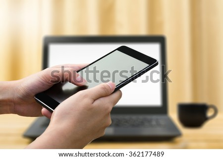 woman hand hold and using mobile,cell phone,smart phone,tablet over blurred image of notebook and coffee background