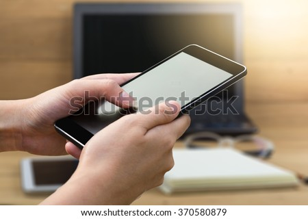 woman hand hold and using smart phone,mobile,cell phone,tablet over blurred image of business office ,blurred image of notebook coffee cup book on wooden table,business concept
