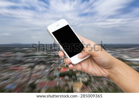 woman hand hold smart phone, tablet,cellphone on blurred landscape of city and sky background - stock photo