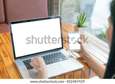 Woman hand hold smart phone with blank empty laptop screen - stock photo