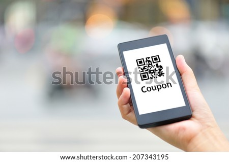 woman hand hold smart phone with coupon QR code in modern city - stock photo