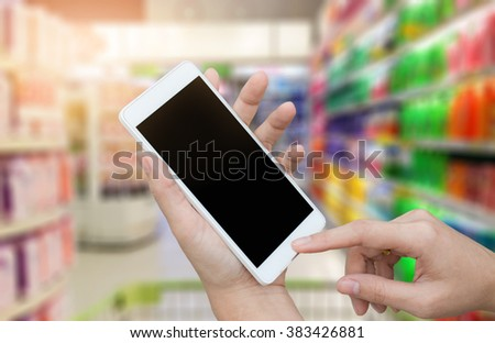 woman hand hold,using and touch screen smart phone, tablet,cellphone over blurred people background in supermarket;shopping by smartphone concept - stock photo