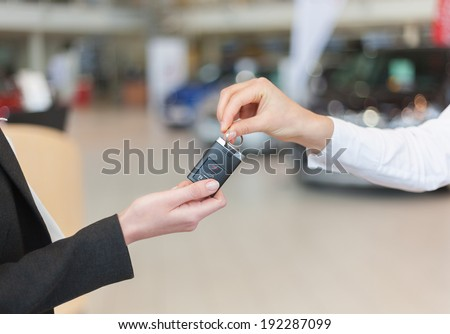 Woman hand holding a car key and handing it over to another person