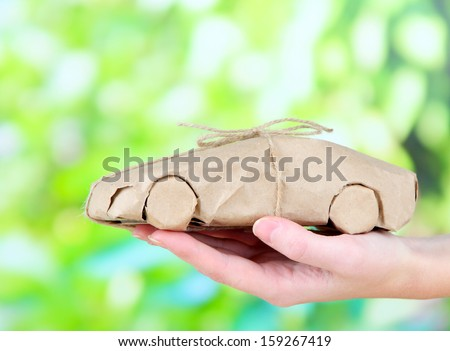 Woman hand holding a car wrapped in brown kraft paper, on nature background - stock photo