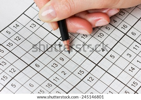 woman hand holding a pencil and solves crossword sudoku, popular puzzle game with numbers - stock photo