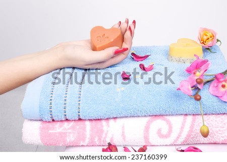 Woman hand holding a soap with heart shape - stock photo