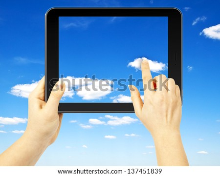 Woman hand holding a tablet on sky background - stock photo