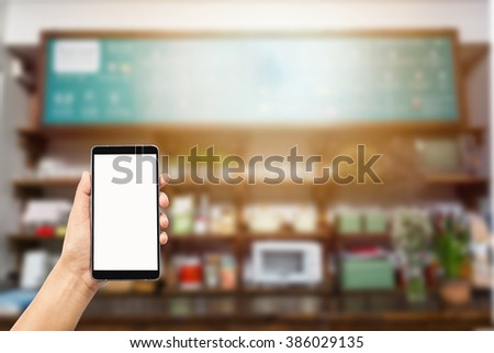 woman hand holding and using isolated screen smart phone,mobile,cell phone on blurred image of coffee shop background,transactions by smart phone concept - stock photo