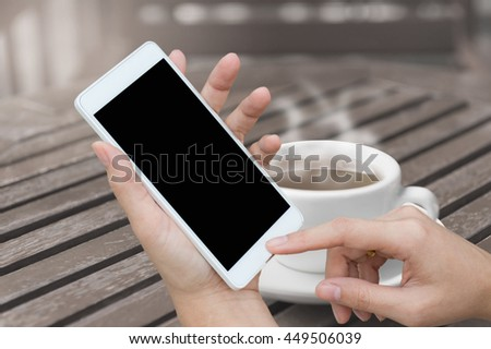 woman hand holding and using mobile (smart phone) blurred image of coffee shop background,technology concept - stock photo