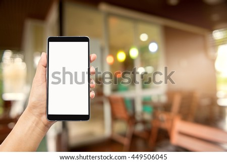 woman hand holding and using mobile (smart phone) blurred image of coffee shop background,techonlogy concept - stock photo