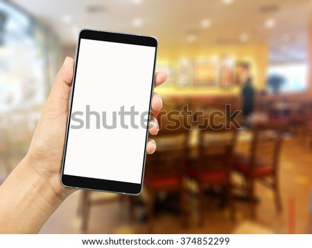 woman hand holding and using the phone tablet on blur restaurant background,Transactions by smartphone concept - stock photo
