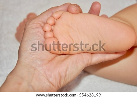 Woman hand holding bare baby feet, close up view