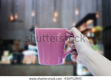Woman hand holding coffee cup with blurred background, stock photo - stock photo