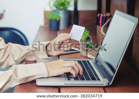 woman hand holding credit card and typing on laptop for online shopping.vintage effect - stock photo