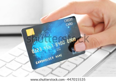 Woman hand holding credit card under keyboard, closeup