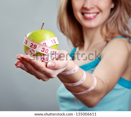 Woman hand holding green apple with diet measurement over grey background - stock photo