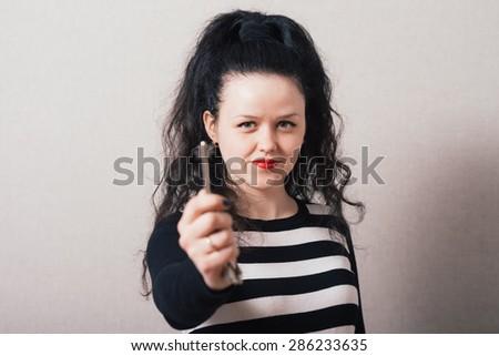 Woman hand holding keys. Gray background - stock photo