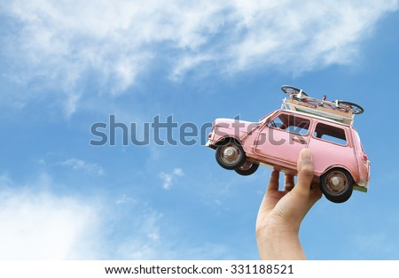 woman hand holding miniature car with blue sky and clouds,(travel concept) - stock photo