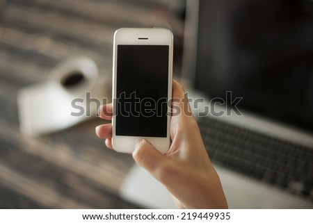 Woman hand holding mobile phone, and laptop and coffee cup  - stock photo