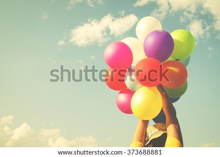 Woman hand holding multicolor balloons done with a retro instagram filter effect - lifestyle concept in summer holiday - stock photo