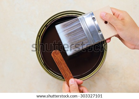Woman hand holding paint brush with wood