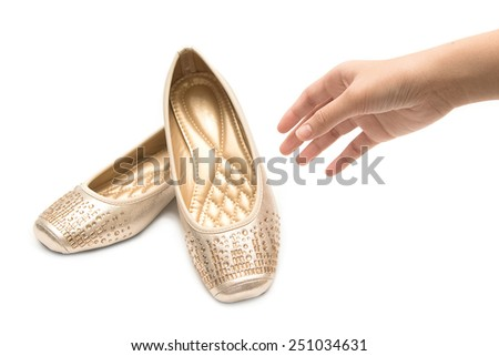 Woman hand holding pair of beige female shoes - stock photo