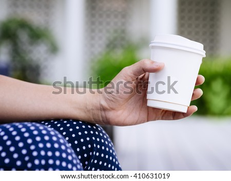 Woman Hand holding Paper Cup coffee Outdoor - stock photo