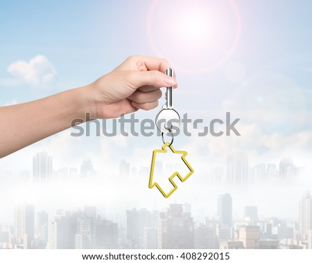 Woman hand holding silver key with golden house shape keyring, on sunny sky cityscape background.