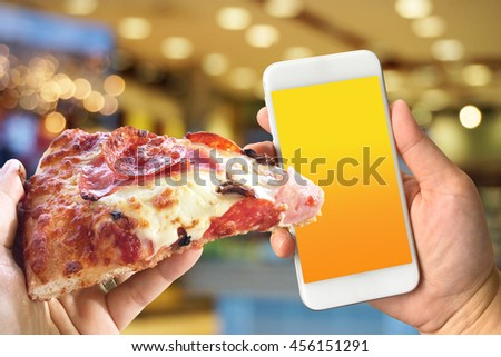 Woman hand holding smartphone against blur colorful bokeh background pizza online concept with copy space - stock photo