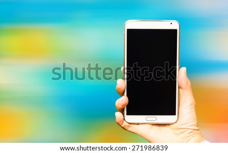 Woman hand holding smartphone against on blurred of background soft focus. - stock photo