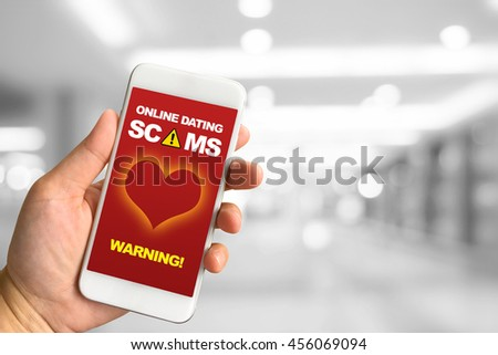 Woman hand holding smartphone against white grey bokeh abstract background online dating scams concept