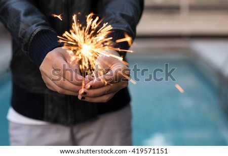 Woman hand holding sparkler outdoors with swimming pool in background - stock photo