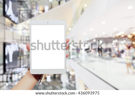 Woman hand holding tablet isolated white screen on blurred shopping mall background, concepts of online shopping through using digital device, smartphone, mobile or tablet - stock photo