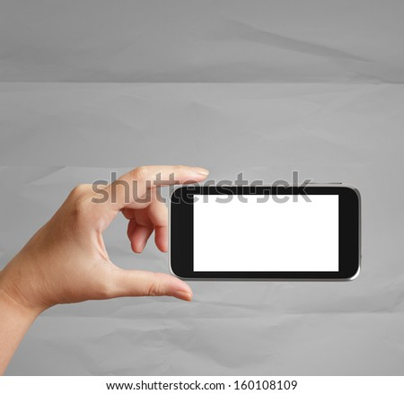 woman hand holding the phone tablet touch computer gadget on crumpled paper background  - stock photo