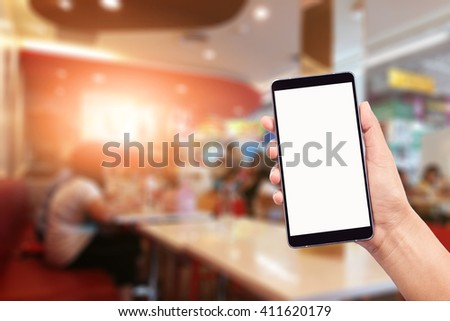 woman hand holding,using and touch smart phone,cell phone,mobile over blurred image of restaurant background,Transactions by smartphone concept - stock photo