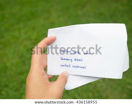 Woman hand holding white paper written day business plan. Meeting team, summary report and meet customers in green background. Business, daily plan, schedule and time management concept. - stock photo