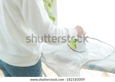 Woman hand ironing a sweater - stock photo