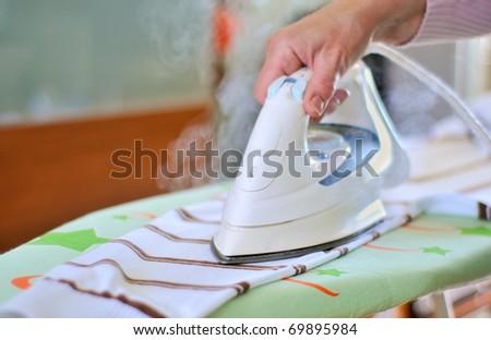 Woman hand ironing a sweater - stock photo