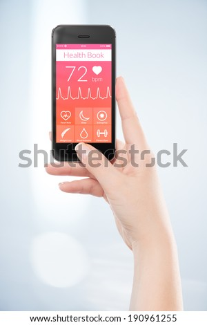 Woman hand is holding black mobile smart phone with health book app on the screen. - stock photo