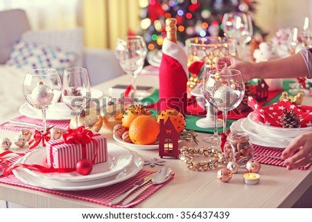 Woman hand lights a candle on holiday table setting