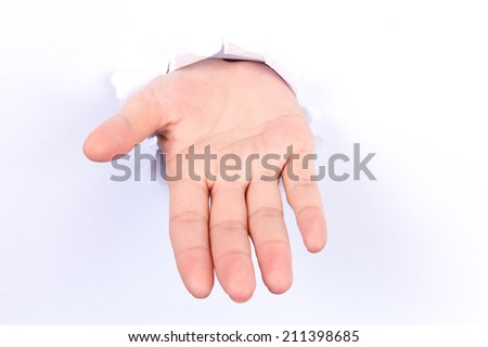 Woman hand making sign through a hole in paper isolated on white