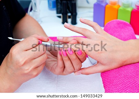 woman hand on manicure treatment with cuticle knife in beauty salon - stock photo