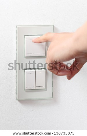 Woman hand operating a light switch